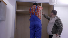 Inserting the shelfs into the wardrobe Stock Footage