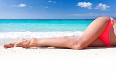 Tan slim legs on beach Stock Photos