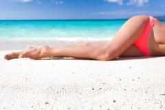 tan slim legs on beach - stock photo