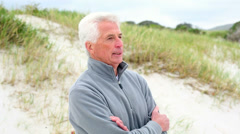 Retired man standing on the beach shivering Stock Footage