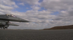C-130 Hercules land while F-16 Fighting Falcon's wait to take off Stock Footage