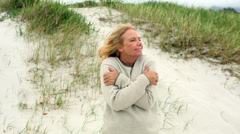 Smiling retired woman shivering on the beach Stock Footage