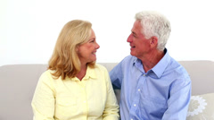 Smiling retired couple being affectionate on the couch Stock Footage
