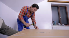 Man hammering the nails into the back of the closet Stock Footage