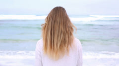 Happy blonde turning and smiling at camera on the beach - stock footage