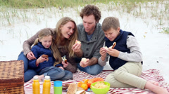 Happy young family having a picnic on the beach Stock Footage