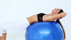 Fit model doing sit ups on exercise ball Stock Footage
