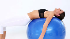 Fit model doing pelvic lifts on exercise ball Stock Footage