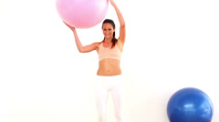 Fit model holding exercise ball and smiling at camera Stock Footage