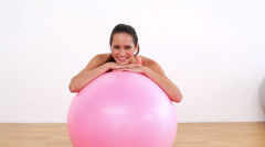 Fit model leaning on pink exercise ball smiling at camera Stock Footage