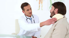 Doctor checking his patient in a neck brace Stock Footage