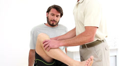 Physical therapist checking patients knee Stock Footage