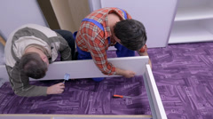 Two guys handle the bed frame with screwdrivers Stock Footage