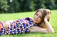 Stock Photo of young woman lying on a green lawn