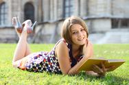 Stock Photo of happy woman reading book on green grass