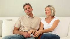 Woman stealing the remote control from her dozing husband on the couch Stock Footage
