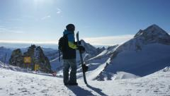 Man with snowboard standing on top of snowy mountain HD Stock Footage