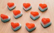 Stock Photo of heart jelly sweets or gummies on wood background.