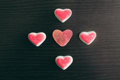 Heart jelly sweets or gummies on dark wood background. overhead shot Stock Photos