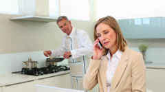 Businesswoman talking on phone while husband cooks dinner Stock Footage