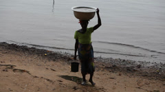 A woman in Ghana takes water from the Volta river b - stock footage