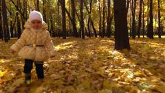 Daughter with mom walk and play in sunny autumn park with yellow leaves. Slow mo Stock Footage