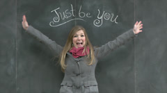 "Cute Girl Stretches Arms Wide & Smiles Under A Chalkboard ""Just Be You"" Sign Stock Footage"