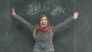 "Stock Video Footage of Cute Girl Stretches Arms Wide & Smiles Under A Chalkboard ""Just Be You"" Sign"
