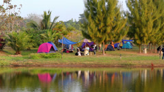Group of people enjoy tent camp beside natural lake Stock Footage