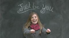 """Cute Girl Dances Under A Chalkboard """"Just Be You"""" Sign Stock Footage"""