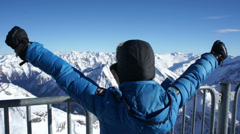 Woman standing on mountain peak with arms outstretched HD Stock Footage