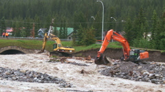 Backhoes trying to control river flood water 01 Stock Footage