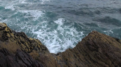 Rocky cliffs and waves crashing the rocks Stock Footage