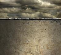 Stock Photo of stormy sky over a concrete wall background
