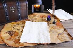Work desk with parchment and old map. Stock Photos