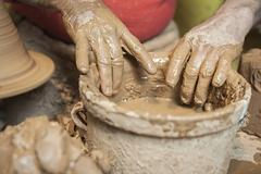 Detail of a potter's hands in a bucket of water Stock Photos
