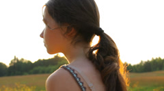 Girl walking in the country in the evening in summer, portrait, sun rays Stock Footage