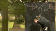 Stock Video Footage of Happy, Silly Couple Next To A Chalkboard Tree In A Park
