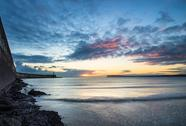 Stock Photo of beautiful vibrant sunrise sky over calm water ocean with lighthouse and harbo