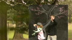 Cute, Playful Couple Having Fun Next To A Chalkboard Tree In A Park - stock footage