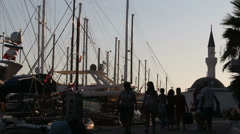 Turkey passersbys silhouetted against boats Stock Footage
