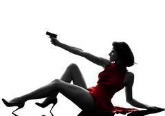 sexy woman holding gun  silhouette - stock photo