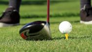 Stock Video Footage of MAN PLACES GOLF BALL ON TEE AND HITS IT | CLOSE UP