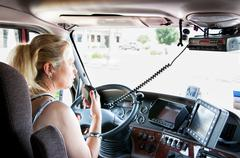 Blonde Woman Truck Driver Talking On Her Radio. - stock photo
