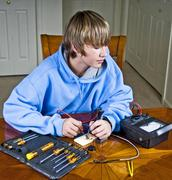 Teenager Using A Voltmeter - stock photo