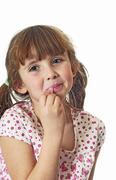 Little Girl Putting On Lip Gloss Stock Photos