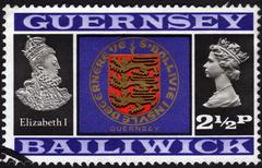 postage stamp issued in guernsey showing a shield and portraits of two queens - stock photo