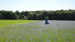 Girl walk blue cornflowers field. Recreation in farmland Stock Footage