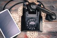 Stock Photo of tablet lying alongside a retro rotary telephone