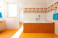 Stock Photo of big orange bath in cute contemporary bathroom